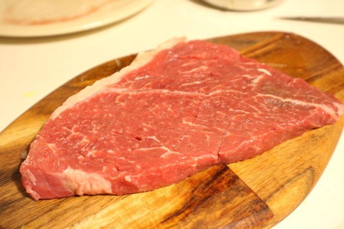 シャリアピンステーキの肉に格子状に切れ込みを入れる