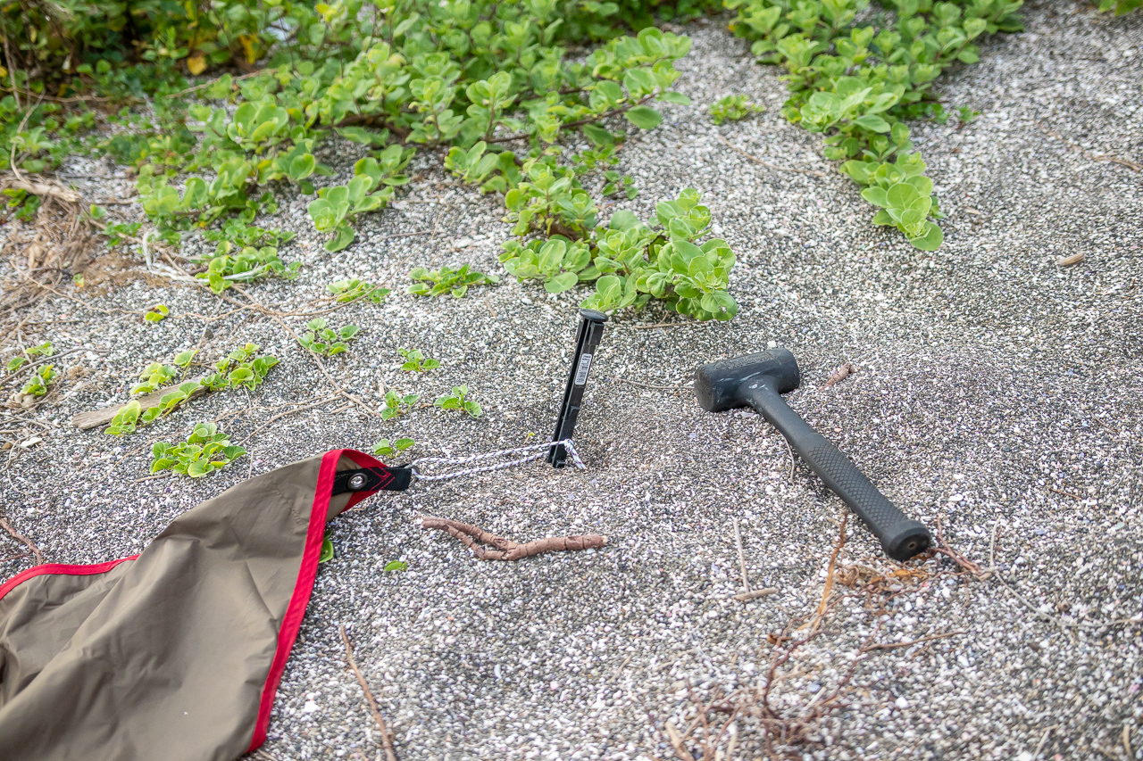 海の砂浜でサンドペグを使用して野営を開始
