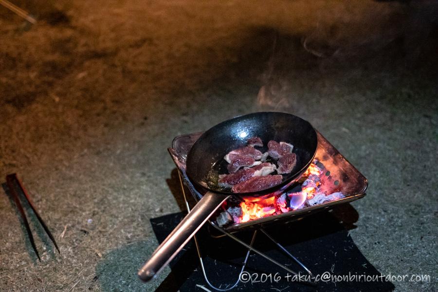 キャンプでイノシシの肉を焼く