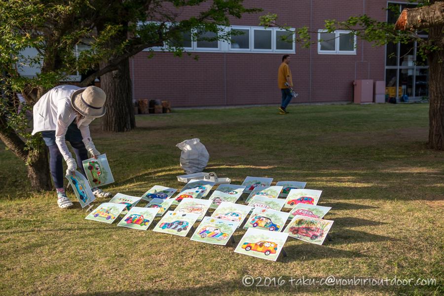 モリパーク アウトドアヴィレッジのクライミングウォール前の芝生の広場で子どもたちの絵を展示中