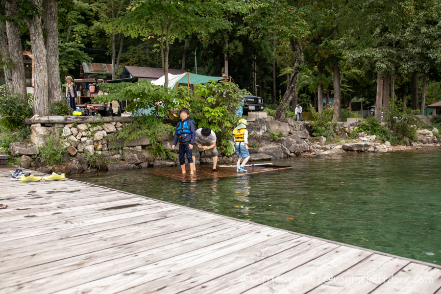 青木湖でSUPを楽しむためにラッシュガードに着替える子ども
